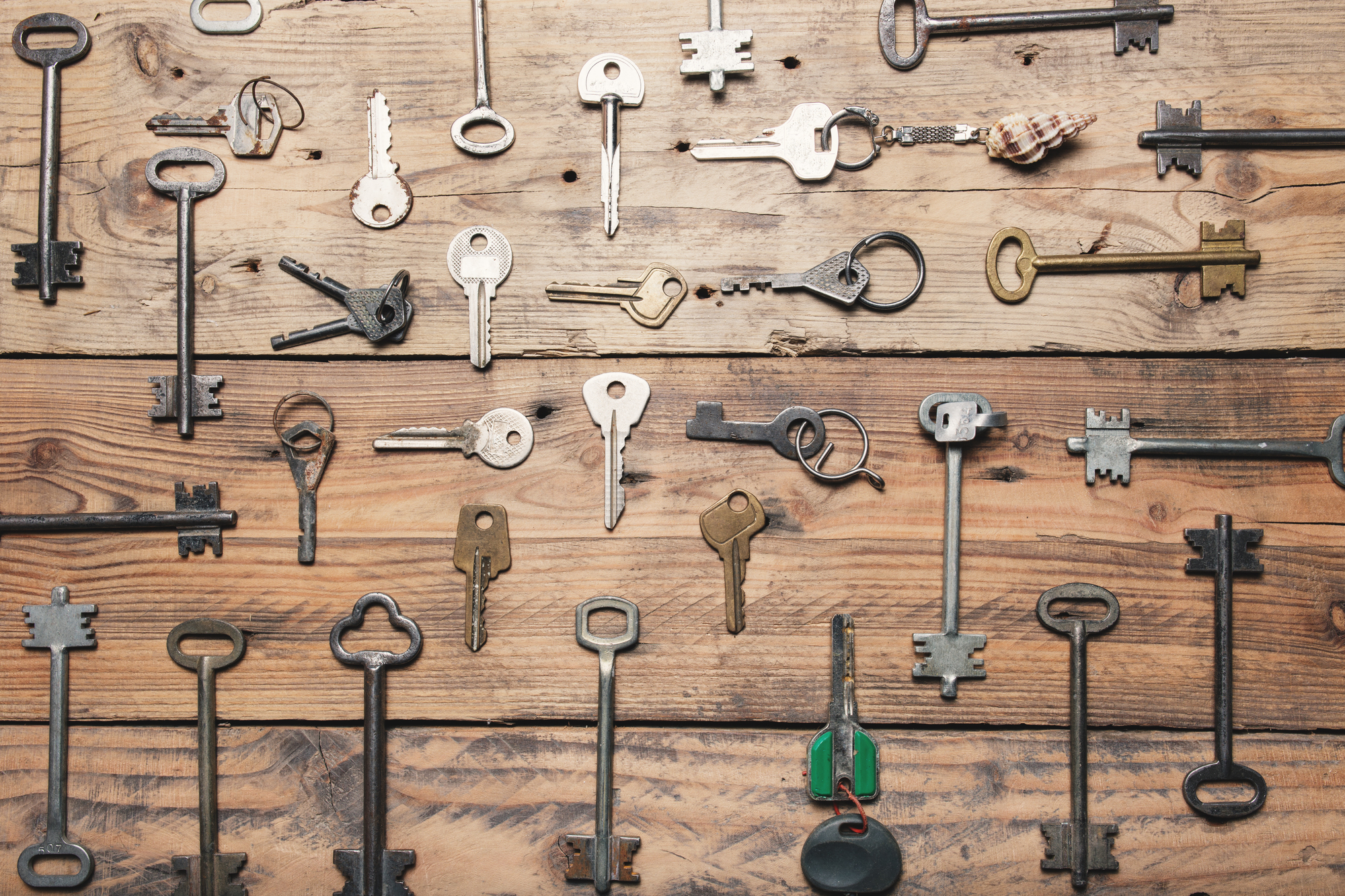 Some door keys aligned on old wooden surface, safety and security concept background.