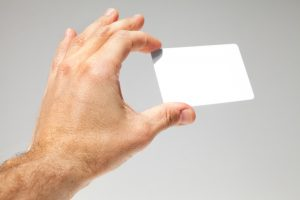 Male hand holds white empty card over gray background, close up photo with selective focus